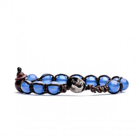 Bracciale unisex Tamashii Classic BHS900-18. Bracciale realizzato con un cordino di cotone, calabash in legno, sfere di agata blu del diametro di 8 mm e bottone metallico di chiusura. Lunghezza regolabile da 16 cm a 23 cm.